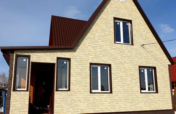Результат оформления дома фасадными панелями Деке Stein Янтарный