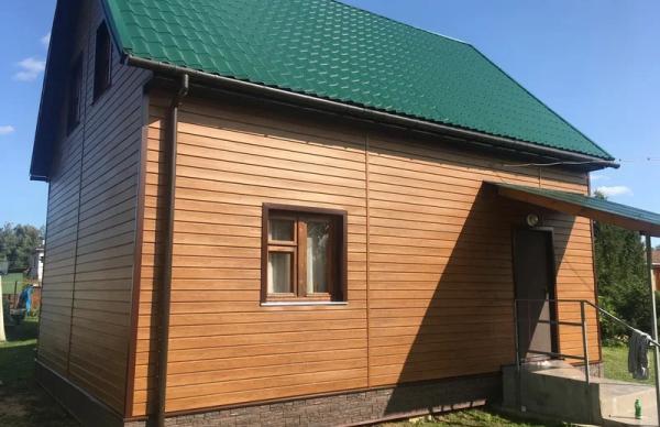 Коричневый сайдинг в сочетании с темно-зеленой крышей